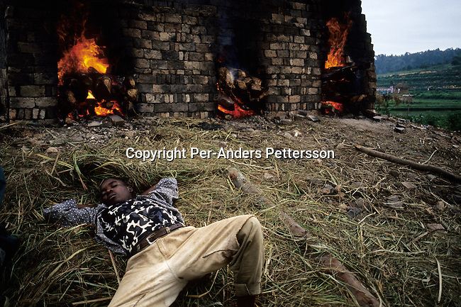 A brick-making factory worker takes a nap early in the morning as he has worked the whole night keeping a fire alight on February 14, 2003. About 100.000 prisoners accused of the genocide are still in prisons nine years later. About 800.000 mainly Tutsis and moderate Hutus were killed in about one hundred days in 1994. Rwanda is currently trying to cope with these huge problems and some prisoners that have confessed to crimes can be tried in village trials. (Photo by: Per-Anders Pettersson)..
