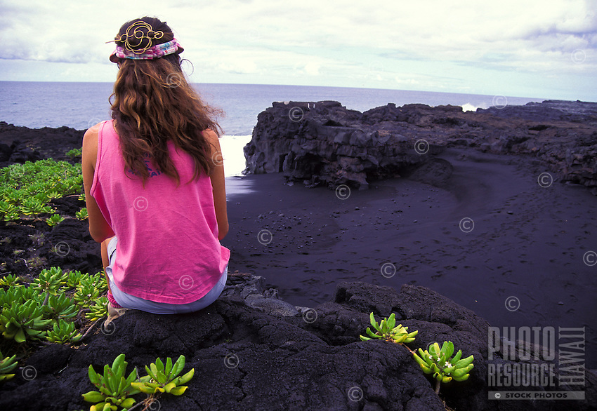 Woman sitting on lava rock near black sand beach. Hawaii Volcanoes National Park, Big Island
