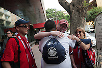 USA's fans (Left to right) Brian Kemp watches as Brent Gamit (back to camera) gives Colin Lamont a hug while Marybeth Kemp looks on outside the Galeria Plaza hotel before boarding a bus to take them to the USA vs. Mexico World Cup Qualifier at Azteca stadium in Mexico City, Mexico on March 26, 2013.