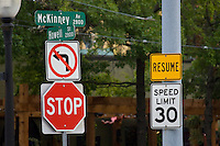 Collection of several somewhat confusing traffic signs at an intersection.