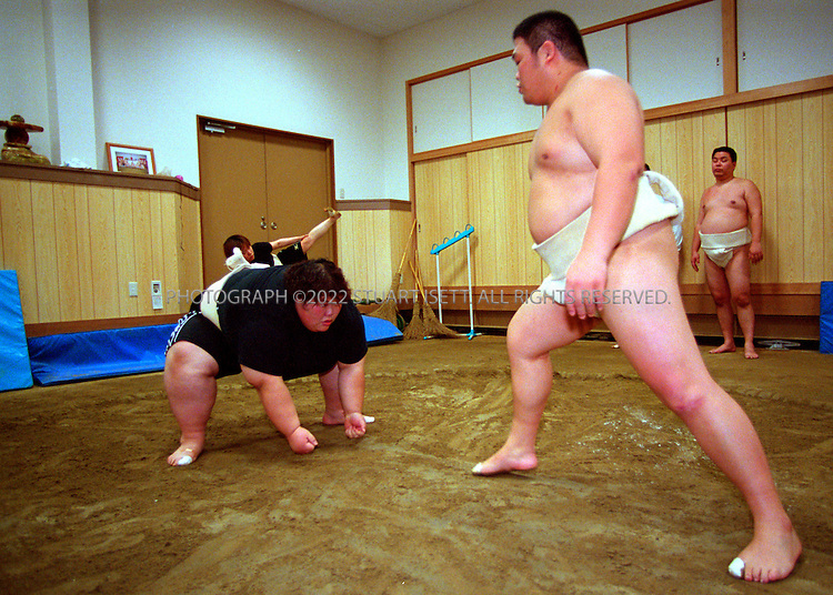 10/26/2001--Osaka, Japan..Rie Tsuihiji, 23, Japan's leading female sumo wrestler and 2000 world champion, practises with a male member of her company's sumo club. With no other large women in the club, Tsuihiji is forced to practise with other men...All photographs ©2003 Stuart Isett.All rights reserved.This image may not be reproduced without expressed written permission from Stuart Isett.