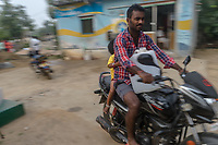 A man carries a plastic can of water on a motorcycle past a Safe Water Network iJal station in village Gorikothapally, Telangana, Indiia, on Friday, February 8, 2019. Photographer: Suzanne Lee for Safe Water Network