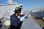 Seaman Tangidenene Quick takes a moment to yell overboard while painting atop the forecastle of the ship on the U.S.S. Green Bay on Jan. 9, 2009 at the Naval Base San Diego in San Diego, California.  The crew is readying the ship for its commissioning in two weeks.