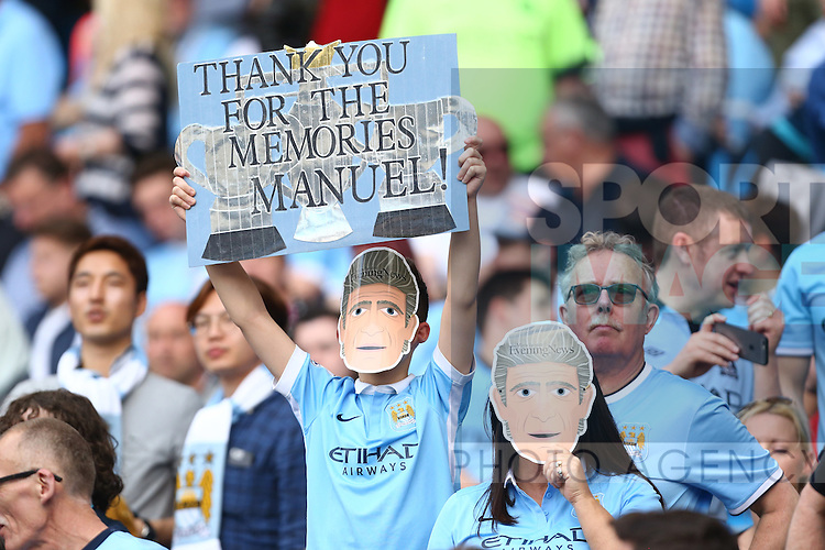 Fans hold up tributes to Manuel Pellegrini, manager of Manchester City during the Barclays Premier League match at the Etihad Stadium. Photo credit should read: Philip Oldham/Sportimage