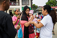 A SPRINT-IPPF humanitarian worker organises a crowd so they can register to receive dignity kits and medicine for pregnant women and lactating mothers at a RH Medical Mission in the Taluksangay Barangay Hall, Zamboanga, Mindanao, The Philippines on November 5, 2013. These Internally Displaced People (IDP) had taken refuge in this Barangay (neighbourhood) after surviving the 3 week long attack by MNLF rebels. Photo by Suzanne Lee for SPRINT-IPPF