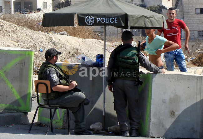 Israeli border guard check a Palestinian man at a newly erected checkpoint in Jerusalem's neighborhood of Jabal al-Mokaber on October 19, 2015. Israeli police began erecting a wall in east Jerusalem to protect a Jewish neighbourhood subject to firebomb and stone attacks launched from an adjacent Palestinian village. Photo by Mahfouz Abu Turk