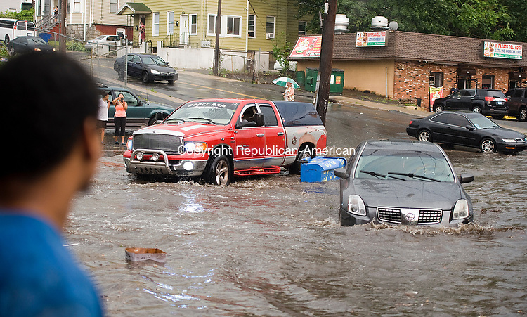 WATERBURY, CT-063017JS07- Zack Oquendo looks on as vehicles drive through the flooded intersection of South Main Street and Washington Avenue in Waterbury on Friday after heavy rains and high winds made its way through the area. <br /> Jim Shannon Republican-American