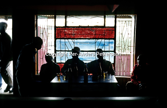 Unidentified people drink in an illegal bar (shebeen) on June 20, 2001 in Site C Khayelitsha, a township about 35 kilometers outside Cape Town, South Africa. Khayelitsha is one of the poorest and fastest townships in South Africa. People usually come from the rural areas in Eastern Cape province to find work as maids and laborers. Most people don't find work and the unemployment rate is very high together with lot violence and a growing HIV-Aids epidemic it's a harsh area to live in. (Photo by: Per-Anders Pettersson).