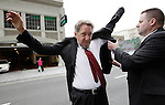 Oracle CEO Larry Ellison, left, puts on his suit as arrives for a court appearance at a federal building in San Francisco, Tuesday, Apriil 17, 2012. Oracle intends to rely heavily on Google's own internal emails to prove Google's top executives knew they were stealing a popular piece of technology to build the Android software that now powers more than 300 million smart phones and tablet computers. (AP Photo/Paul Sakuma)