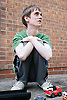 Teenage boy with Autism looking up from playing with toy vehicles,