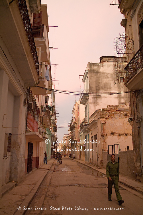 Man in uniform walking through a city street at dusk, Havana, Cuba.