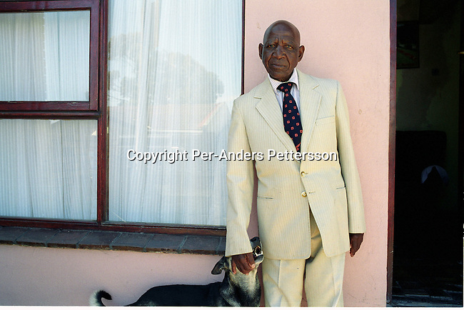 "GUGULETU, SOUTH AFRICA - FEBRUARY 18: Dan Ndzabela, age 82, plays with his dog on outside his house on February 18, 2004 in Guguletu, a township outside Cape Town South Africa.  He was one of the first to be forced out of District Six, a lively area in Cape Town, that was declared ""white only"" during Apartheid. Dan was forced to move in 1959 to a grim township outside Cape Town and he always wanted to return. On February 11, this year, he was given a key from former President Nelson Mandela at a ceremony celebrating the first finished houses and the start of the return for residents forced away many years ago. .Photo: Per-Anders Pettersson/iAfrika Photos......."