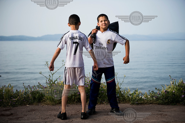 Two Afghan boys wearing Real Madrid T-shirts pose for a portrait, after having made the journey to Greece on an inflatable boat. Their boat landed on the beach of Skala Sykaminias, Lesbos island after crossing the narrow six mile strait betwen the Turkish coast and Greece. Every day hundreds of refugees, mainly from Syria and Afghanistan, are crossing in small overcrowded inflatable boats the 6 mile channel from the Turkish coast to the island of Lesbos in Greece. Many spend their life savings, over $1,000, to buy a space on these boats.