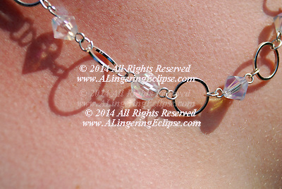 Elongated shadows of a crystal and silver necklace reflect on teen's skin in dramatic light.
