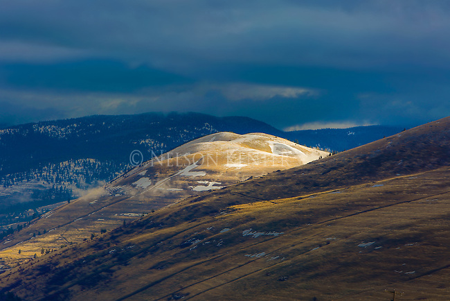 The sun lights the top of Mount Jumbo in early spring in Missoula, Montana.