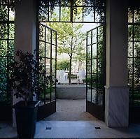 The marble-floored reception room leads out through double glass-paned doors to a gravelled terrace overgrown with jasmine