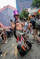 New York, NY- Gay Pride Parade in the West VIllage - Parade marcher on a Segway with an American Flag umbrella on Greenwich Street in the Far West Village.