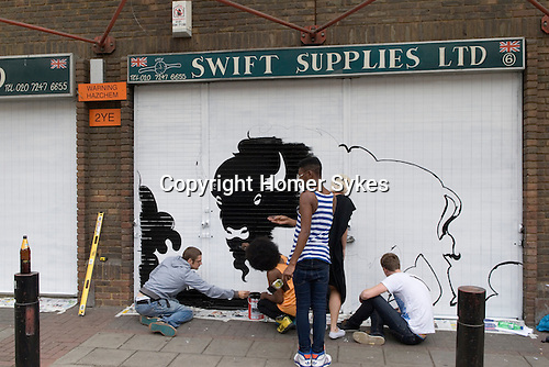 Jasper Goodall ( extreme left ) street artist making an art work New Goulston Street London E1. Just off Middlesex Street. Co-ordination by Jessica Tibbles in black dress from the Electric Blue Gallery.