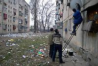 ROMANIA, 12.2006; Bucharest..Installing parabolic antenna, Rahova area, Bucharest, Romania..© Egyed Ufo Zoltan / Est&Ost Photography