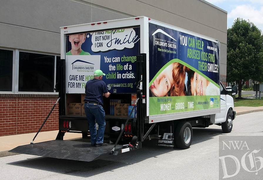 STAFF PHOTO SAMANTHA BAKER &bull; @NWASAMANTHA<br /> <br /> Steve Schotta, executive director for the Northwest Arkansas Children's Shelter, closes the door of the new truck the Shelter received from the Walmart NW Arkansas Championship golf tournament Friday, June 20, 2014, at Mondelez International's office in Rogers. The larger-scale truck allows the NWA Children's Shelter to more easily pick up donations than their previous method.