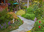Vashon-Maury Island, WA<br /> Stone pathway leads through perennial gardens featuring salvia, sedum, thyme, spirea and grasses to covered patio