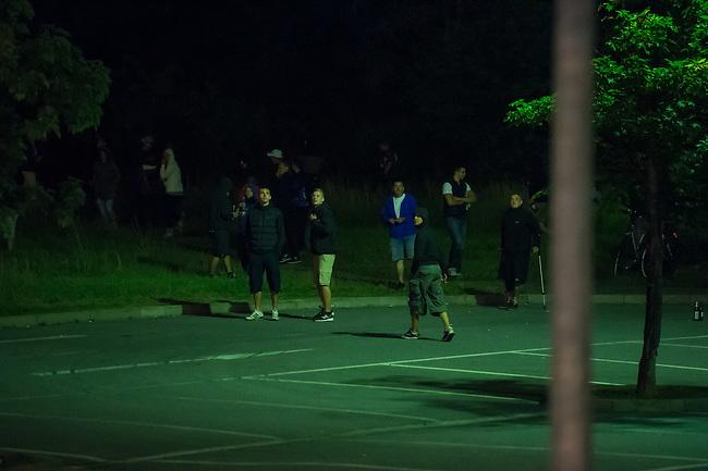 Nach den pogromartigen Ausschreitungen gegen eine Fluechtlinsunterkunft im saechschen Heidenau am Freitag den 21. August 2015 durch Anwohnerinnen der Ortschaft, kamen am Samstag de 22. August 2015 ca. 250 Menschen in die Ortschaft um ihre Solidaritaet mit den Gefluechteten zu zeigen.<br /> Am Vorabend hatten Rassisten, Nazis und Hooligans sich zum Teil Strassenschlachten mit der Polizei geliefert um zu verhindern, dass Fluechtlinge in einen umgebauten Baumarkt einziehen. Ueber 30 Polizisten wurden dabei verletzt.<br /> Bis in die Abendstunden des 22. August blieb es trotz spuerbarer Anspannung um die Unterkunft ruhig. Im Laufe des Tages wurden immer wieder Gefluechtete mit Reisebussen gebracht was von den wartenenden Heidenauern mit Buh-Rufen begleitet wurde. Vereinzelt wurde auch &quot;Sieg Heil&quot; gerufen, was die Polizei jedoch nicht verfolgte.<br /> Kurz vor 23 Uhr griffen Nazis und Hooligans wie am Vorabend die Polizei mit Steinen, Flaschen, Feuerwerkskoerpern und Baustellenmaterial an. Die Polizei mussten mehrfach den Rueckzug antreten, scheuchte den Mob dann von der Fluechtlingsunterkunft weg. Dabei wurden auch wieder Traenengasgranaten verschossen. Mindestens ein Nazi wurde festgenommen.<br /> Im Bild: Angreifer ziehen sich ins Dunkle zurueck.<br /> 22.8.2015, Heidenau/Sachsen<br /> Copyright: Christian-Ditsch.de<br /> [Inhaltsveraendernde Manipulation des Fotos nur nach ausdruecklicher Genehmigung des Fotografen. Vereinbarungen ueber Abtretung von Persoenlichkeitsrechten/Model Release der abgebildeten Person/Personen liegen nicht vor. NO MODEL RELEASE! Nur fuer Redaktionelle Zwecke. Don't publish without copyright Christian-Ditsch.de, Veroeffentlichung nur mit Fotografennennung, sowie gegen Honorar, MwSt. und Beleg. Konto: I N G - D i B a, IBAN DE58500105175400192269, BIC INGDDEFFXXX, Kontakt: post@christian-ditsch.de<br /> Bei der Bearbeitung der Dateiinformationen darf die Urheberkennzeichnung in den EXIF- und  IPTC-Daten nicht entfernt werden, diese s