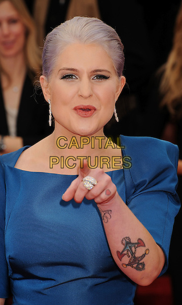 Kelly Osbourne (wearing Zac Posen).Arrivals at the 69th Annual Golden Globe Awards at The Beverly Hilton Hotel, Beverly Hills, California, USA..January 15th, 2012.globes half length dress blue black structured shoulders tattoos dyed grey gray hair hand finger pointing ring .CAP/GDG.©GDG/Capital Pictures