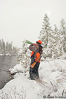 Man using a moose call in the wilderness in the snow.