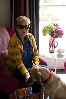 Nicky Tibbles and her dog sitting in the cosy reading area situated on the half -landing of her Notting Hill home