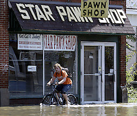 A man rides his bike on Main Street as flood waters from the Blanchard River start to recede after heavy rains caused flooding Thursday, August 23, 2007, in Findlay, Ohio. The Blanchard River was close to 7 feet above flood stage at Findlay yesterday morning, the highest since a 1913 flood.