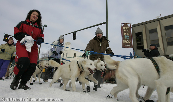 Musher Jim Lanier and handlers walk their dogs to the start line on Anchorage's 4th avenue.