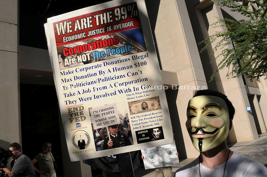 Phoenix, Arizona. September 17, 2012 - A small crowd of demonstrators in Phoenix, Arizona gathered to mark one year since the beginning of the Occupy Movement that opposes Wall Street and large corporations that represent the one percent who control wealth in the United States. A protester with the Occupy Phoenix Movement demonstrates against the Wells Fargo bank in Downtown Phoenix during the first anniversary of the Occupy Wall Street Movement. Photo by Eduardo Barraza © 2012