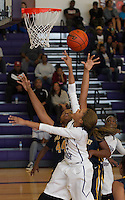 Cedar Ridge Raiders Imani Robinson attempts to shoot over Stony Point's Jaiton Walls Saturday at Cedar Ridge.  The Raiders defeated the Tigers 66-58.