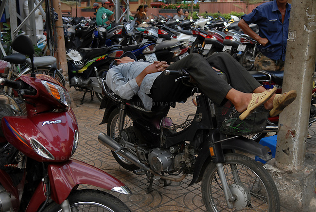 "A motor bike driver called a ""xe om"" takes a name while waiting for customers in Ho Chi Minh City, Vietnam."