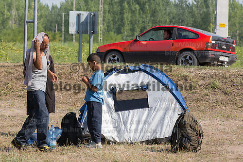 Illegal migrants wait for police dispatch in near Asotthalom (about 190 km South of capital city Budapest), Hungary on August 13, 2015. ATTILA VOLGYI