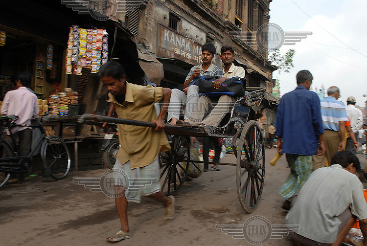 A rickshaw wallah transports two passengers through a crowded market street.