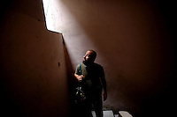Photographer: Rick Findler..06.10.12 A sniper belonging to the Free Syrian Army peers out of a window while walking up a stairwell in the city of Aleppo, Syria. There is a vast number of snipers in the city creating extreme danger for anyone roaming the streets.