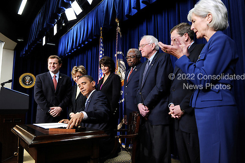 Washington, DC - December 9, 2009 -- Left to right: United States Representative Tom Perriello (Democrat of Virginia), U.S. Senator Barbara Boxer (Democrat of California), U.S. House Majority Whip James Clyburn (Democrat of South Carolina), U.S. Senator Bernard Sanders (Independent of Vermont), U.S. Senator Kent Conrad (Democrat of North Dakota) and U.S. Secretary of Health and Human Services Kathleen Sebelius look on as U.S. President Barack Obama, center, signs a memorandum making 500 million U.S. dollars of Recovery Act funds available to renovate and upgrade community health care centers across the U.S. in the South Court Auditorium in the Eisenhower Executive Office Building (EEOB), Wednesday,  December 9, 2009 in Washington, DC..Credit: Olivier Douliery / Pool via CNP