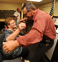 NWA Democrat-Gazette/ANDY SHUPE<br /> John Schuster (right), a detective with the Washington County Sheriff's Office, hugs Myrrah Mueller (left) of Farmington during a ceremony to award the Muellers with the American Police Hall of Fame Medal of Honor at the University of Arkansas Police Department in Fayetteville. Mueller's husband, West Fork Police Chief Paul Mueller, was shot and killed on March 20, 1981, while making a traffic stop in West Fork following a robbery in Fayetteville. Schuster, then an officer with the Fayetteville Police Department, was shot twice as he exchanged gunfire with the suspects four days later.