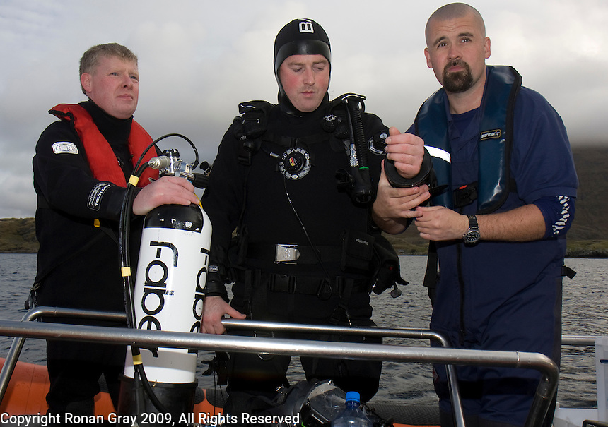"Saturday Oct 10 2009.  SCUBADIVE WEST, GALWAY, IRELAND:  Dive supervisor Gary Jennings (L) and Commercial Diver Tiernan Gray (R) ""dress-in"" Paul Devane before his world record attempt diver.  Brothers Declan and  Paul Devane began their world record attempt to be the first divers to stay underwater on SCUBA for a period of 24-hours at 10am this morning."