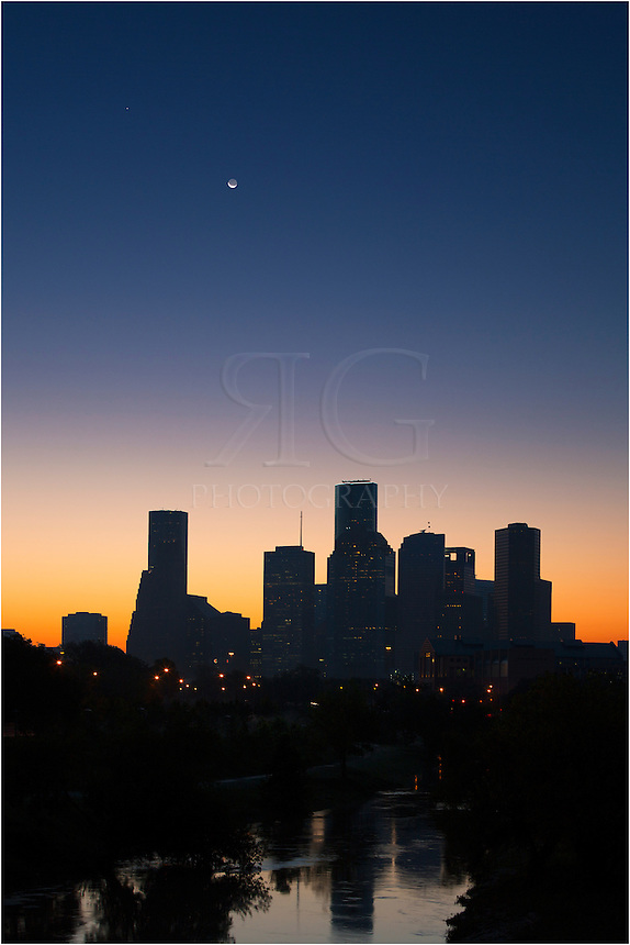 On a crystal clear morning in the largest city in the Lone Star State, a crescent moon rises over the Houston skyline about 30 minutes before sunrise. In the foreground are the waters of Buffalo Bayou and beyond that, the fading lights of downtown.