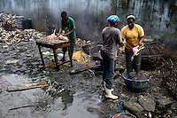 NIGERIA, Lagos, Arena Market , selling of live chicken which are immediately butchered here , background cow horns of slaughtered cows / Verkauf von lebenden Huehnern und Schlachtung vor Ort