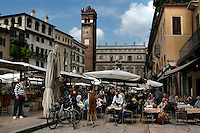 General view of busy cafe, Piazza delle Erbe, Verona, Italy. The Piazza delle Erbe (Square of Herbs) stands on the old Roman Forum, and remains the centre of city life, with a colourful market, cafes for meeting friends, and the city's administration. In the background are the 14th century Gardello Tower and the Baroque Palazzo Maffei. Picture by Manuel Cohen.