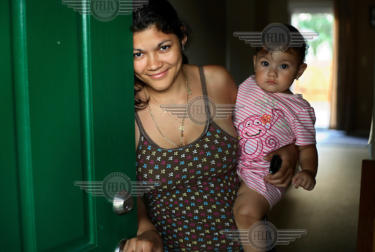 25 year old Elsie Savalba, a Honduran immigrant, stands in the doorway of her home in Manassas, Virginia with her one year old daughter Alison. Her house has plummeted in value over the last year from 295,000 USD to 150,000, and for the past six months Elsie has not been paying her mortgage. Soon they will be moving out. The area is suffering from a major collapse in the housing market following the subprime crisis and global credit crunch, which has forced the foreclosure and abandonment of numerous properties.