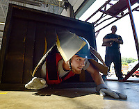 NWA Democrat-Gazette/BEN GOFF &bull; @NWABENGOFF<br /> Zack Hutcheson of Elkins, currently with the Elkins Volunteer Fire Department, emerges from the search maze on Saturday Aug. 15, 2015 at Springdale Fire Department station No. 1 as he and other prospective firefighters take the Candidate Physical Ability Test. Candidates have 10 min, 20 sec. to complete a course with eight events, all while wearing a 50 lbs. weight vest. Candidates have three opportunities over several weeks to pass the test, earning certification that will be recognized by participating departments around the country as part of the application process for firefighting positions.