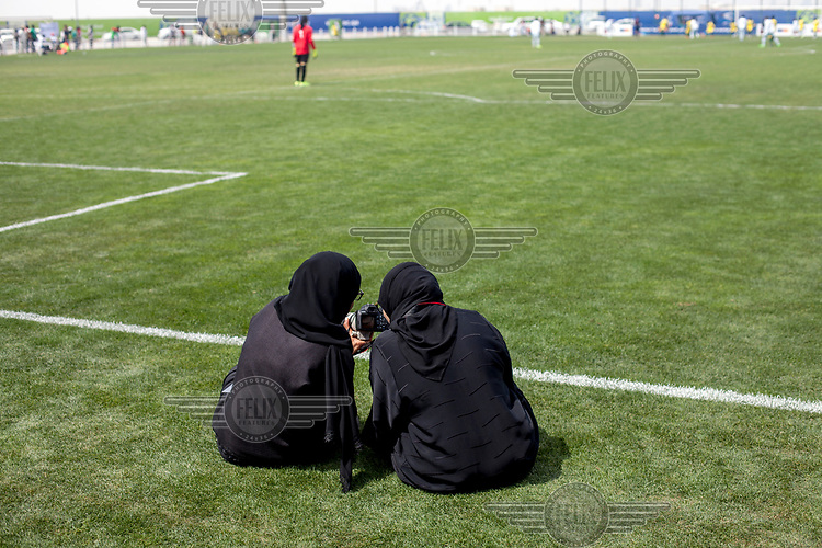 Two women check their images while taking pictures during a photography workshop at the Workers' Cup 2017, a competition for employees from across the emirate.
