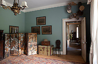 An antique screen decorated with Victorian decoupage fills a corner of this ante-room