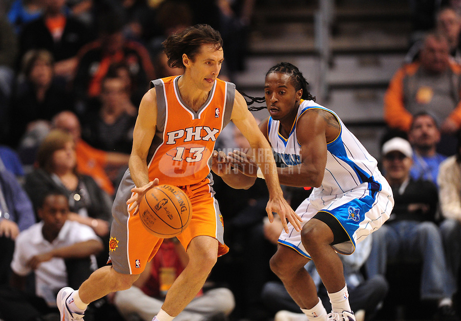 Dec. 26, 2011; Phoenix, AZ, USA; Phoenix Suns guard Steve Nash (left) controls the ball against New Orleans Hornets guard Cardell Johnson at the US Airways Center. The Hornets defeated the Suns 85-84. Mandatory Credit: Mark J. Rebilas-USA TODAY Sports