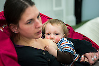 A mother breastfeeding her young toddler while chatting to other mums at a breastfeeding support drop-in centre.