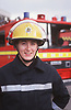 Female firefighter wearing uniform standing on forecourt of fire station with fire engine in background,